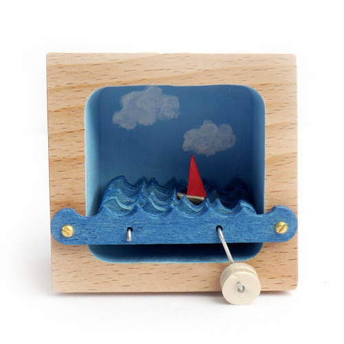 Kinetic Sailboat Sculpture with Blue Sky and Clouds