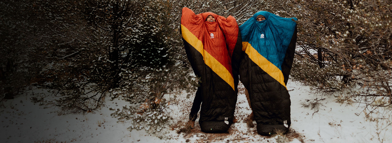 Couple wearing SD Nitro Quilts in the snowy woods