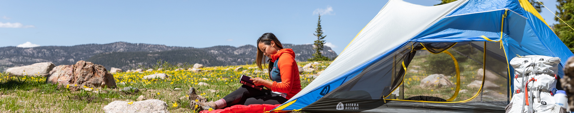 Woman sitting next to a Sierra Designs tent