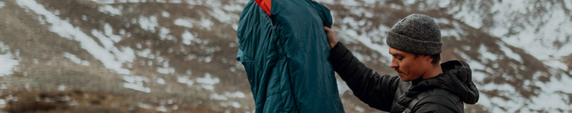 Man holding a Sierra Designs sleeping bag