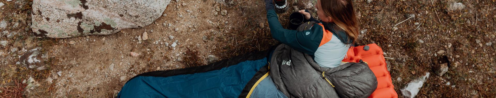 Woman making coffee while inside SD sleeping bag