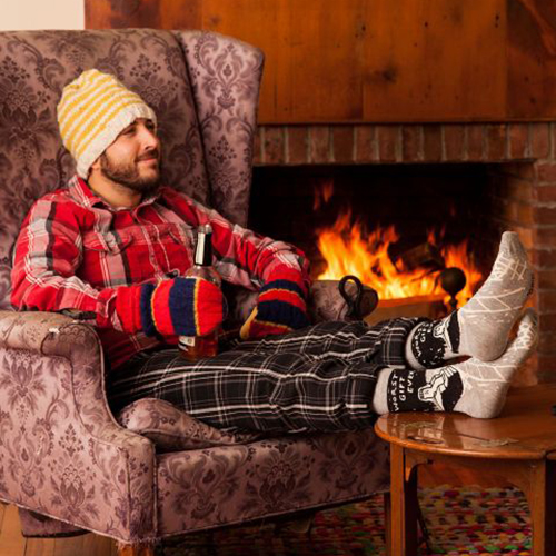 Blue Q Men's Socks 'Worst Gift Ever' in front of a fireplace | the design gift shop