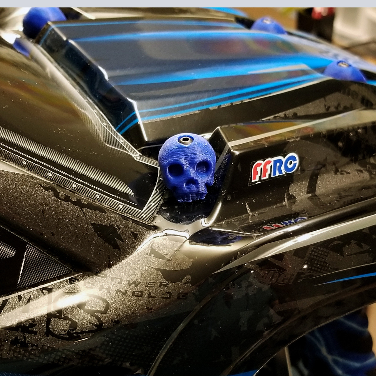 X-MAXX Skull Body washers by Fullforce RC.  Showing the Passenger side in Blue.