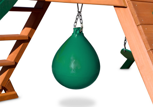 Green punching ball attached to underside of swing set deck on white background.