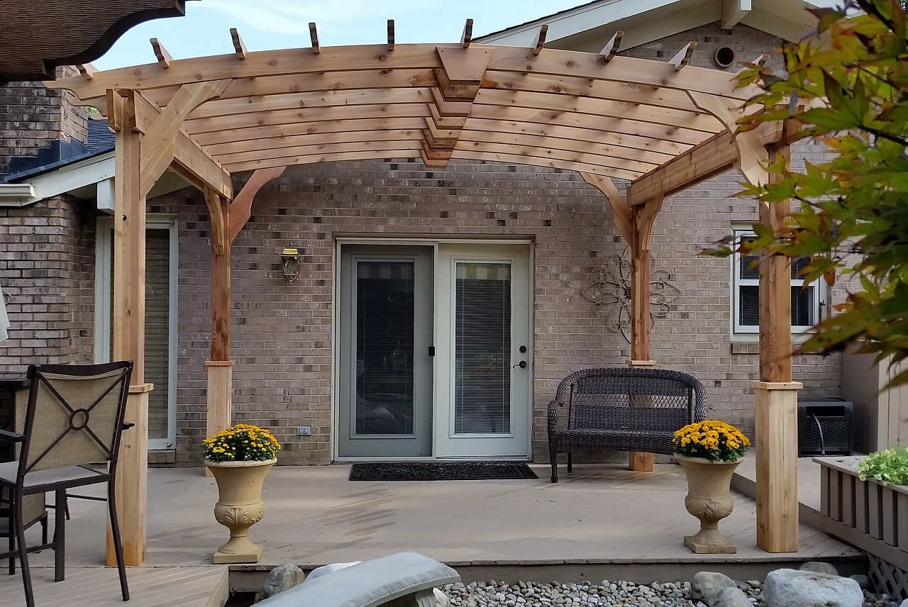 12x9 pergola kit with curved top creates an entrance way to double doors over this wooden deck.