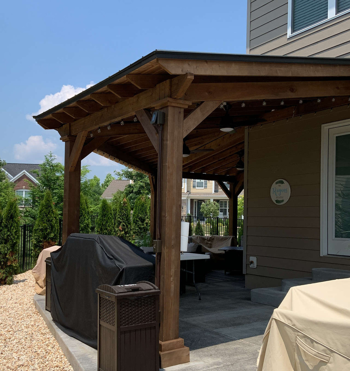 48x12 wall-mounted wrap-around cedar Lean-To Pavilion. Black metal panel roofing. Walnut color stain. Chesterfield, MO.