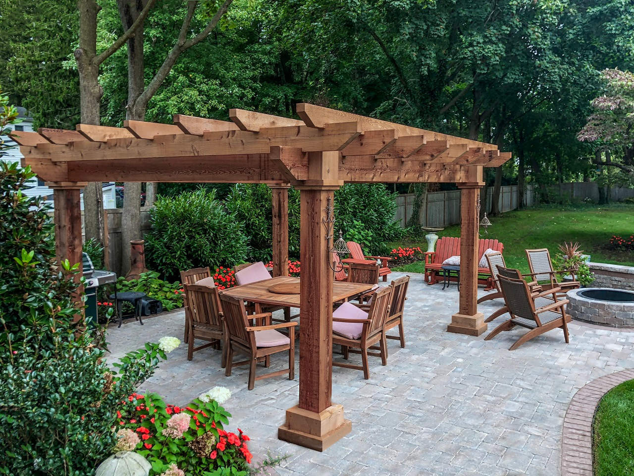 This customer expanded their backyard dramatically by creating a living space in the corner of their yard complete with a rough sawn cedar pergola, wood dining set, fire pit and Adirondack chairs all set on stone pavers.