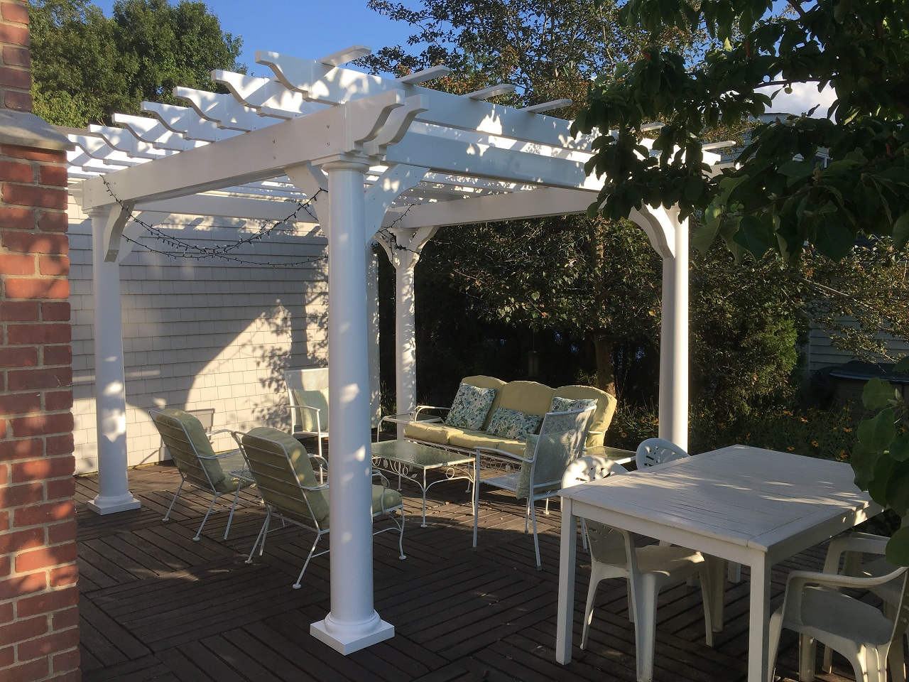 This customer created a cozy outdoor living space with plenty of privacy with a 10x10 vinyl pergola, furniture and card table.
