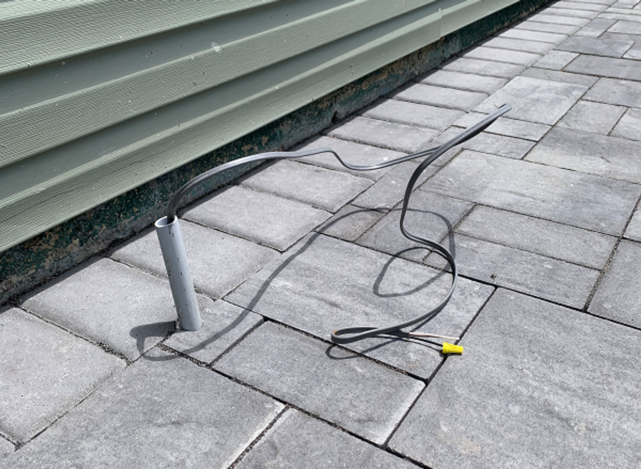 """""""Stub-up"""" PVC conduit carrying electrical wire."""
