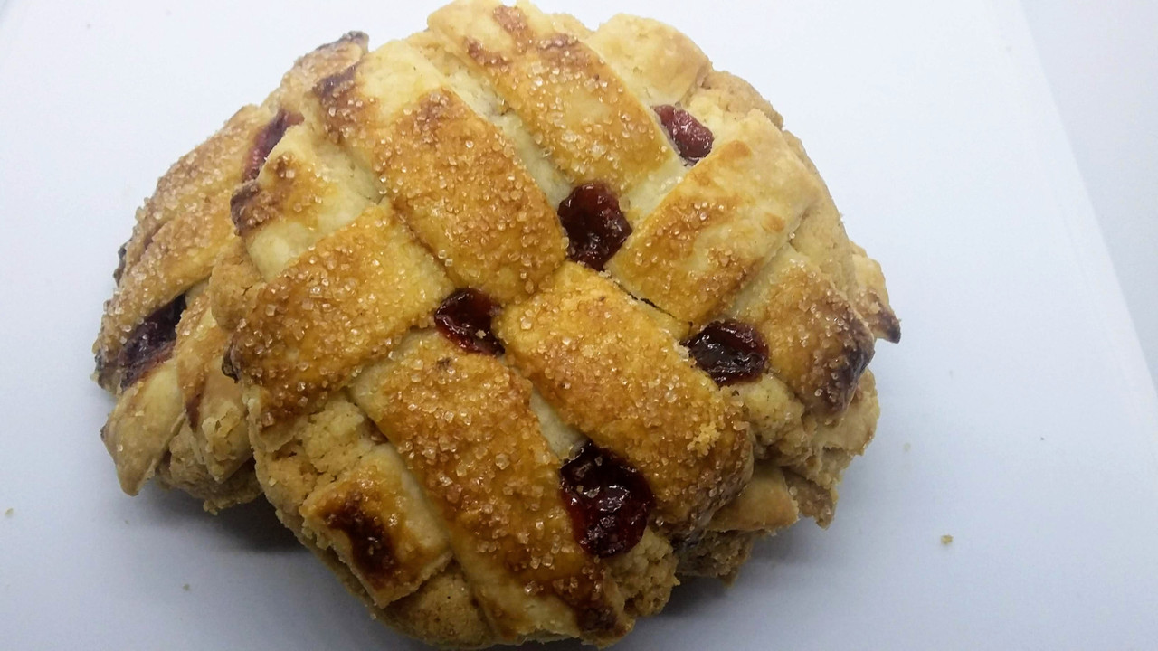 Mountain berry pie filling and sugar cookie crust lattice butter pie crust sprinkled with raw sugar.