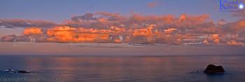 Clouds lit by sunrise from Paritutu