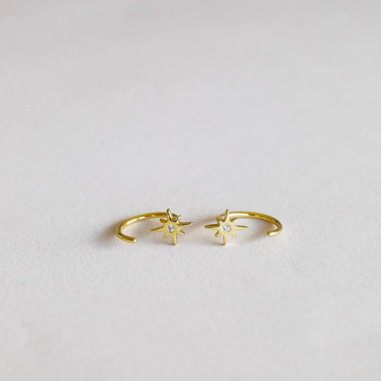 """Our dainty Star Huggies will stand out from the rest and are perfect for everyday wear. Loop these through and let this pair """"hug"""" your ears tight. Featuring a petite CZ stone cut into shape and set in an 18k gold-plated huggie earring over sterling silver."""