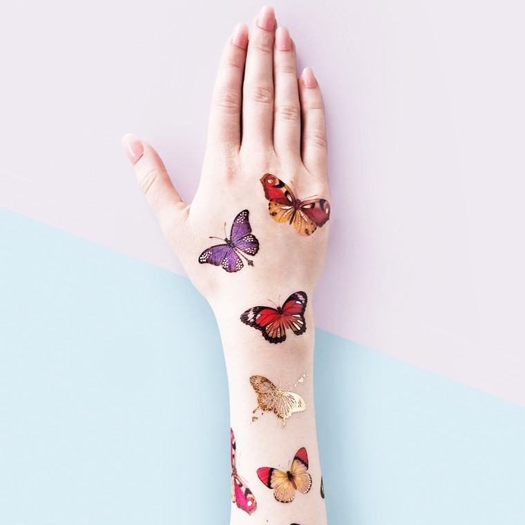 """Butterflies Temporary Tattoos   Realistic tattoo design Long lasting Perfect for any occasion Designed in London  Easy to apply: - Cut out the desired design - Peel off the plastic - Place design face down onto clean skin - Wet with water and peel paper off! Ta dah!  To remove: - Soak tattoo with baby oil, or oil based make up remover, to allow the adhesive to dissolve.  - After 10 seconds, remove the oil with a cotton pad. - Be gentle when removing, do not rub the skin hard particularly around the eye area.  Each pack contains 2 sheets of design Metallic and colour, 4"""" x 4"""".  Woman Owned - Not on Amazon"""