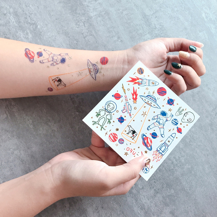 """UFO Temporary Tattoos  Realistic tattoo design Long lasting Perfect for any occasion Designed in London  Easy to apply: - Cut out the desired design - Peel off the plastic - Place design face down onto clean skin - Wet with water and peel paper off! Ta dah!  To remove: - Soak tattoo with baby oil, or oil based make up remover, to allow the adhesive to dissolve.  - After 10 seconds, remove the oil with a cotton pad. - Be gentle when removing, do not rub the skin hard particularly around the eye area.  Each pack contains 2 sheets of design Metallic and colour, 4"""" x 4"""".  Woman Owned - Not on Amazon"""