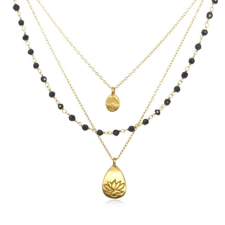 """A string of onyx beads rests between two fine chains.  Tree of life - deep grounding, faith. Lotus - new beginnings, infinite potential. 18 karat gold plated over brass.  Onyx - endurance, perseverance, grounding. 18"""" length. Lotus pendant - 0.687"""" long."""