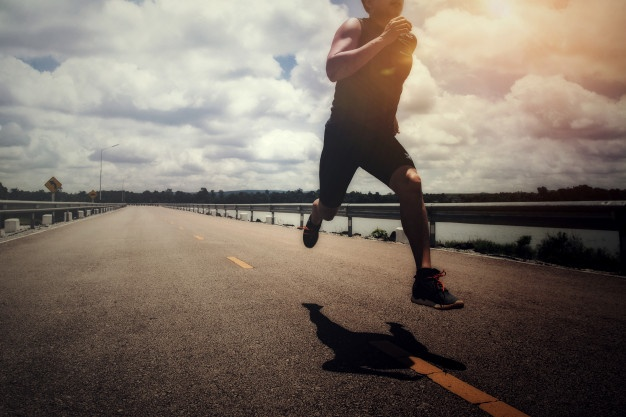 Shot of man in mid-air as he runs down the road