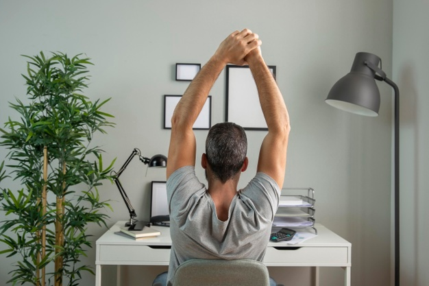 Man reaching his arms up to stretch at his desk
