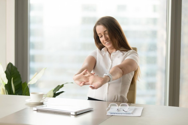 Woman in white shirt stretching her arms and hands in an office