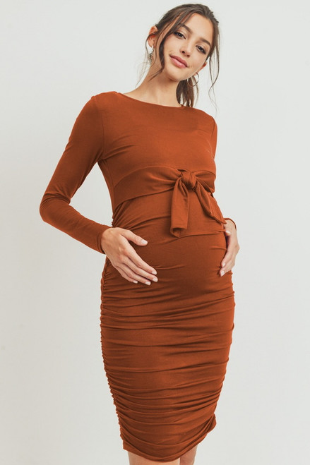 A rust long sleeve maternity dress featuring a front tie and side ruching. Wear this dress during pregnancy and afterward! Lift front tie detail for convenient access to chest for nursing or to pump!