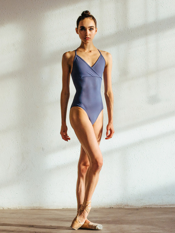 The Naomi Wisteria Leotard, a halter styled leotard with a cross front detail.  Wisteria is a muted purple color.