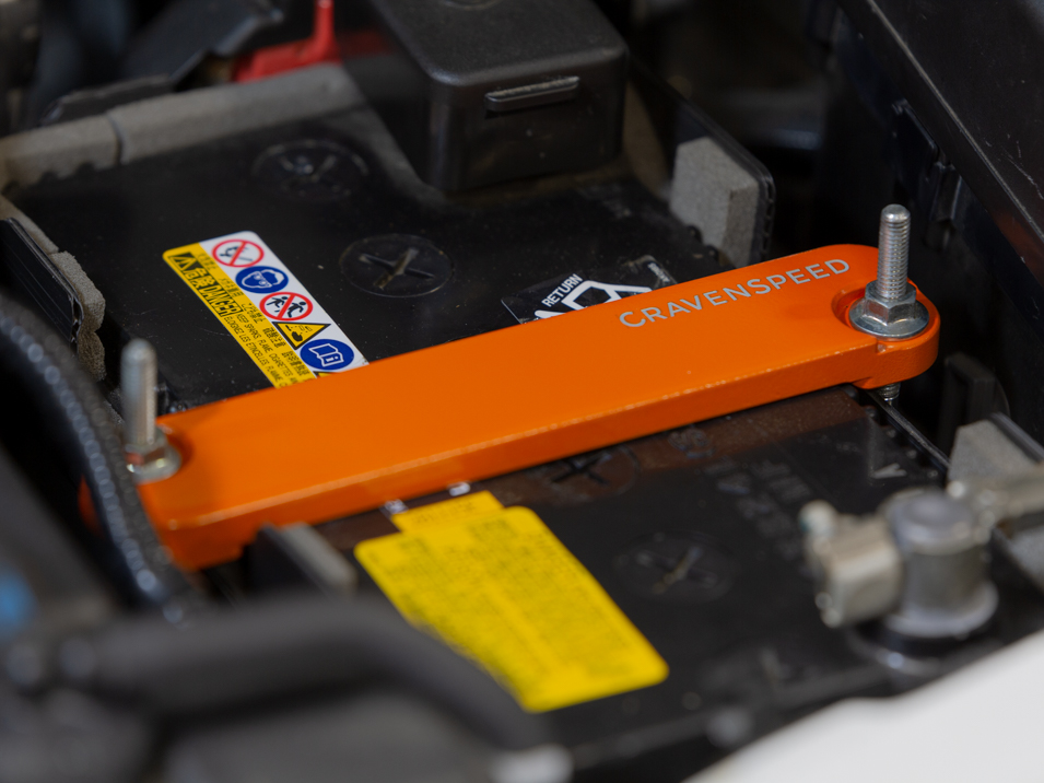 The CravenSpeed Battery Tie Down for the ND Mazda Miata/MX-5 in 30th Anniversary Orange.