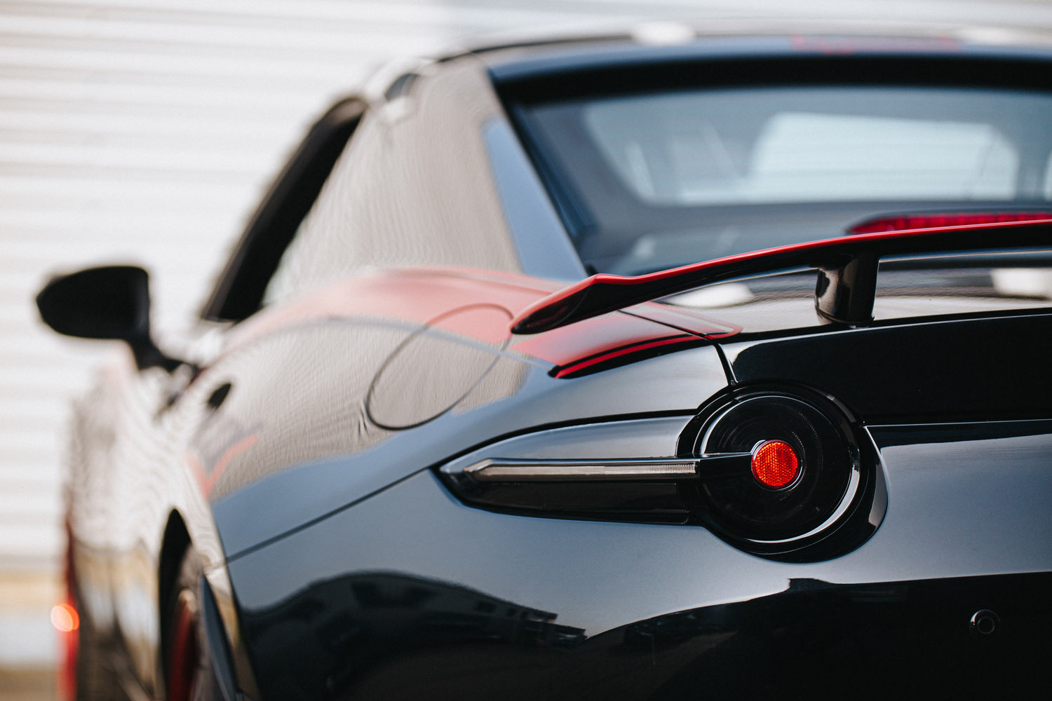 Close up image of Tinted Tail Lights installed on a black ND Miata