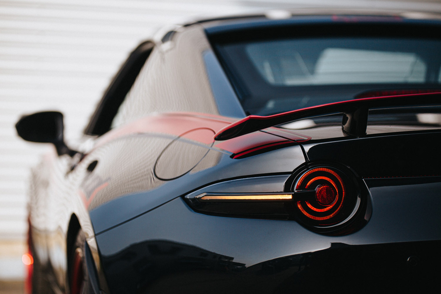Close up image of partially lit up Tinted Tail Lights installed on a black ND Miata