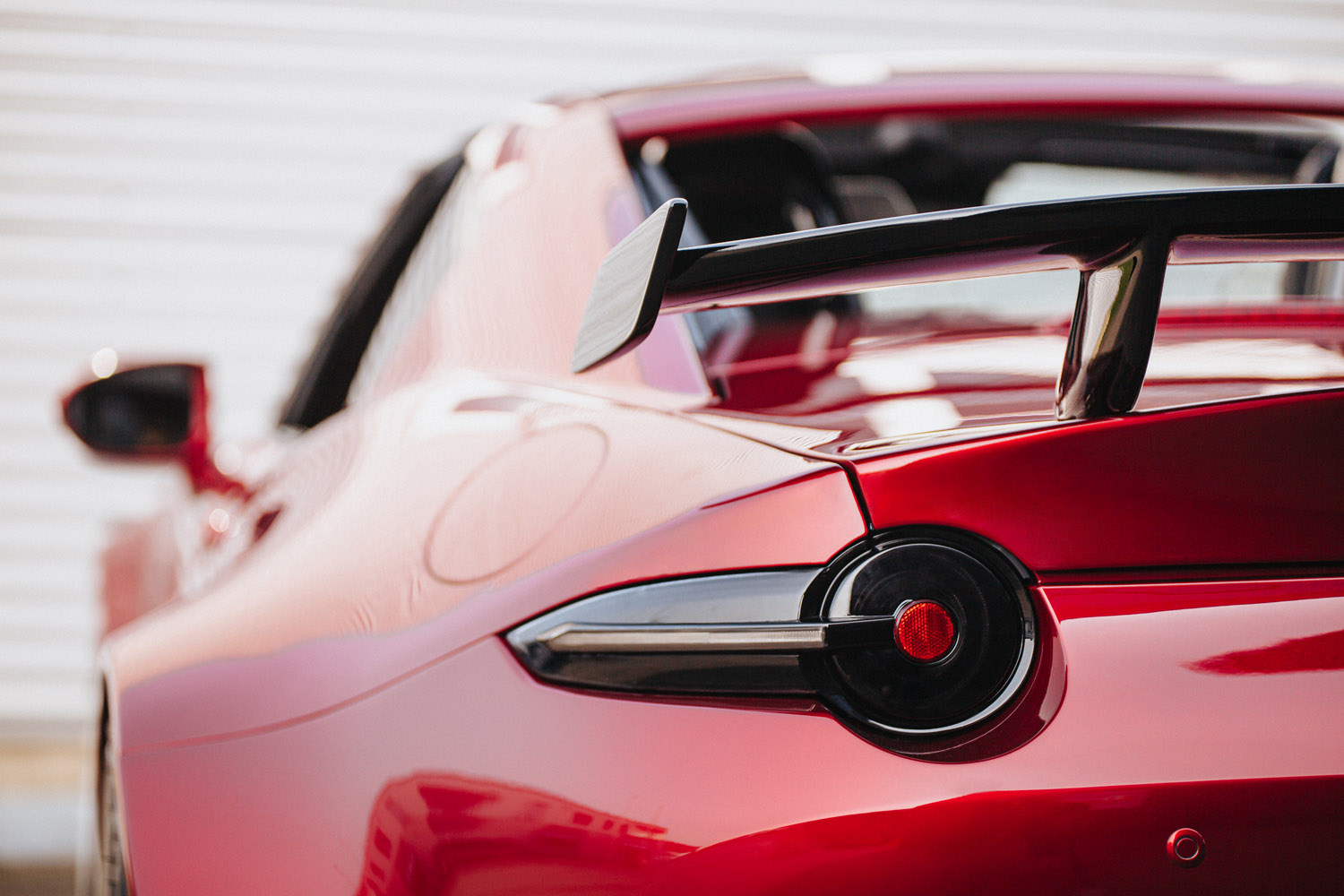 Close up image of Tinted Tail Lights installed on a red ND Miata