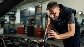 Auto mechanic looking at engine