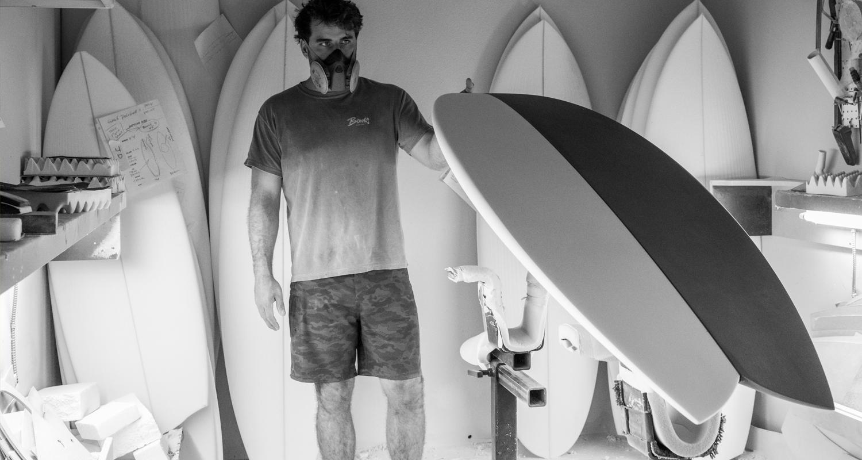 """Surfboard shaper wearing 19"""" Maui Rippers  boardshorts in surf shop"""