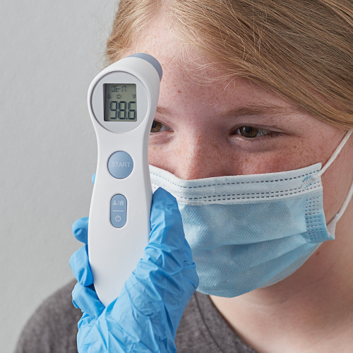 This image is of a person with a latex glove on taking a temperature reading on a child using the DET-306 infrared thermometer that is FDA approved.