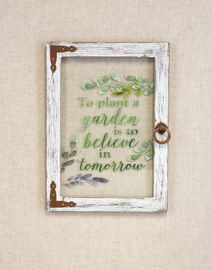 "Glass window with wooden frame measures 81/2"" W. x 1/2"" D. x 12"" H  Printed in green: ""To plant a garden is to believe in tomorrow"""