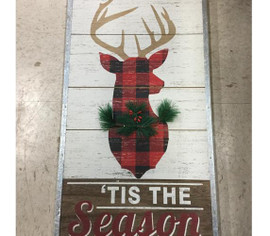 "''Tis the Season' to celebrate the holidays with this classy stag on a wood plank panel trimmed with riveted tin. Stag silhouette With plaid fill and dimensional faux fir trim looks great with classic, lodge, country, farmhouse, or rustic decor. 13 ""W x 23 1/4"" x 1/2"" D"
