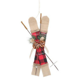 """Burlap skis ornament with red and black plaid fabric on the middle of each ski. Two ski poles with greenery and pine cone accents. Skis and poles are crossed over each other to form an X. Made of foam, fabric, wood, and paperboard. 16"""" H x 9"""" W x 2""""D."""