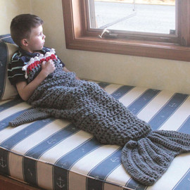 """This whimsical shark tail blanket is the coolest way to keep warm! Acrylic blanket features hand knit shark design. One size fits most kids and adults. Handwash only. Material: Acrylic Size: 56"""""""
