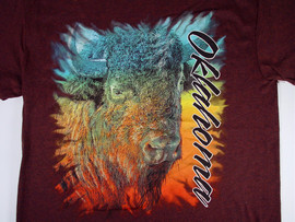 "An artistically rendered bison with a rainbow of watercolor accents. ""Oklahoma"" in script vertically down left side of shirt."