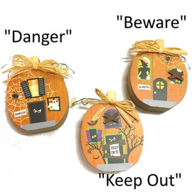 "Whimsical 4"" tall x 1"" thick wood pumpkin blocks to perch on shelf or windowsill, with different scenes of haunted houses and dimensional wood accents. Choose ""Danger"" with spiderweb and ghost, ""Keep Out!"" With bats and tree, or ""Beware"" with witch. All have raffia bow stem.  Sold individually."