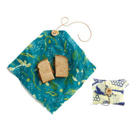 """Wrap up your sandwich and snacks for on-the-go meals. Our sandwich wraps include hemp twine and a sweet (made-in-Vermont!) bee button. Plus, they double as a handy place mat in the cafeteria or during a picnic. Bee's Wrap® is the sustainable, natural alternative to plastic wrap for food storage. Reusable. Wash in COOL water with a mild dish soap. Let air dry. Made of beeswax, organic cotton, organic jojoba oil and tree resin. Includes: 1 x Bees + Bears print sandwich wrap 13"""" x 13"""" (33 x 33cm) 1 x Oceans print sandwich wrap 13"""" x 13"""" (33 x 33cm)"""