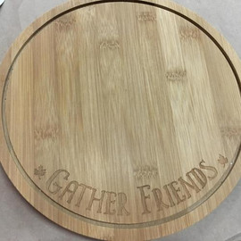 "10"" diameter cheeseboard is footed and has ""Gather Friends"" engraved on the front. Channel for catching liquid runoff around edge. Made of sustainable bamboo."