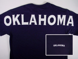 "Navy blue shirt with white screen lettering ""Oklahoma"" across shoulders on back."