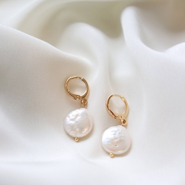 Pearl huggie earrings lay close to the earlobe for a flash of natural beauty. 18K gold plated hoop with natural pearl accent.