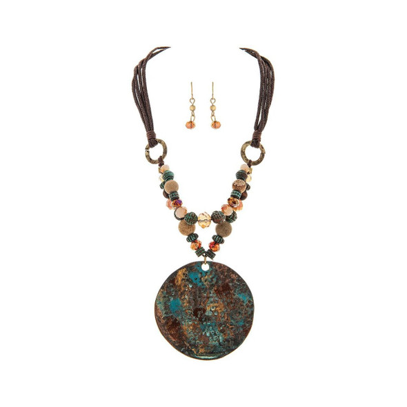 """Large patina copper medallion necklace with four cords and adjustable chain (from 10-12"""") accented with verdigris, natural, faceted and pearlescent beads in turquoise, verdigris, amber and warm tones. Faceted metallic beaded earrings complete the set. Fish Hook earrings hang 1/2 inch. Medallion measures 2 1/2"""" across, necklace has lobster clasp and chain to allow adjustment. Medallion hangs center chest when adjusted to longest length."""