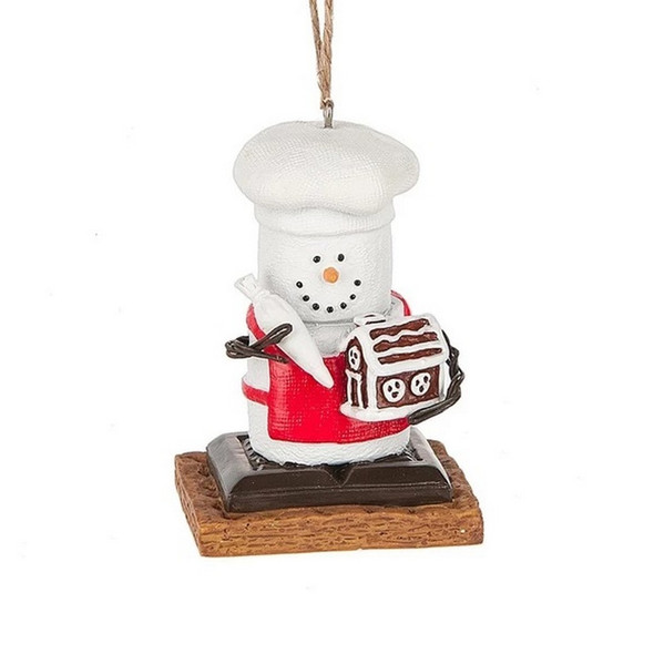 Collectible Marshmallow S'more ornament wearing a chef hat and Santa suit holds a gingerbread house. Seasonally available collectible.
