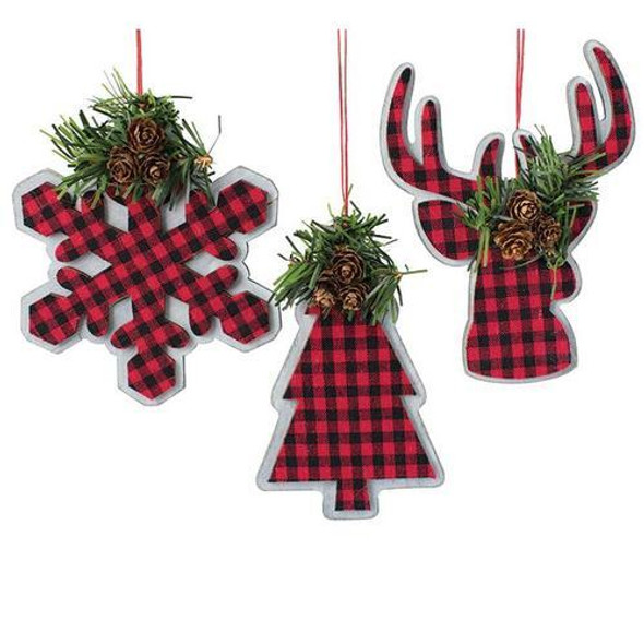 """Wood ornaments that have a whitewashed back with red and black plaid fabric layer adhered on the top. Choose snowflake, Christmas tree and reindeer shape with greenery on the top and red twine hanger.  6"""" H x 3 1/2"""" W  6"""" H x 4 1/2"""" W  6"""" H x 4"""" W  Approximately 9"""" H with hanger."""
