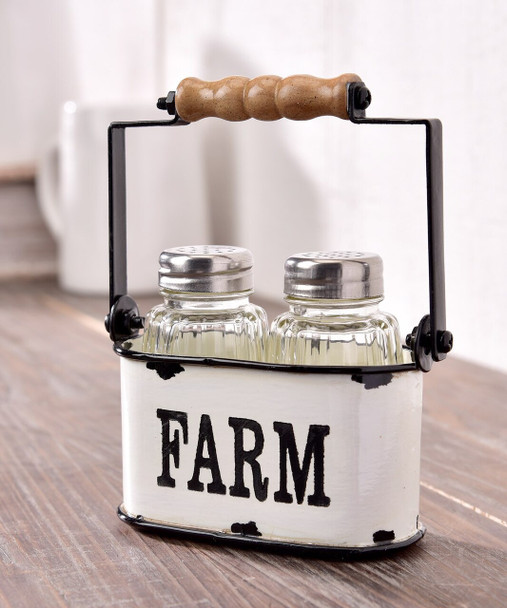 Two clear glass salt and pepper shakers sit neatly inside of this white holder designed with a black metal and wood handle and a FARM sentiment in black typography. FDA Approved. Steel, MDF, Glass.