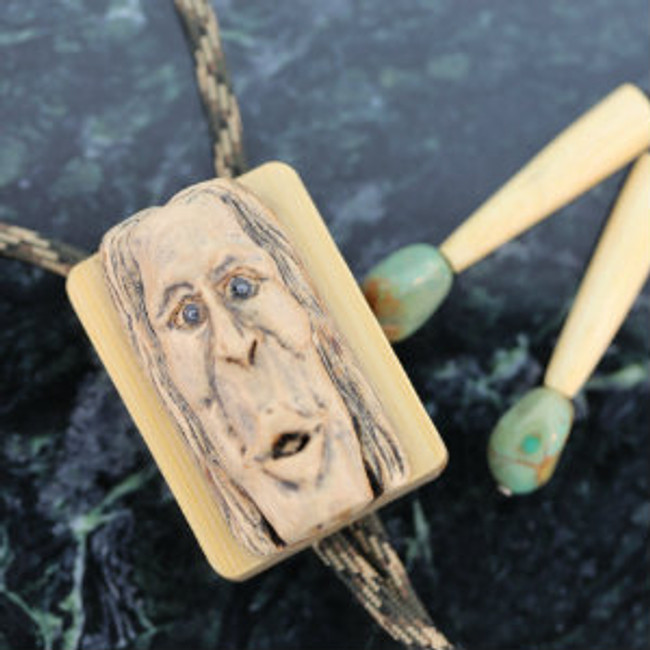 Bolo. Whimsical carving of a long-faced man on maple wood. Hematite eyes. Patterned paracord. Mounted on natural color bamboo wood. Bamboo tips with turquoise ends.
