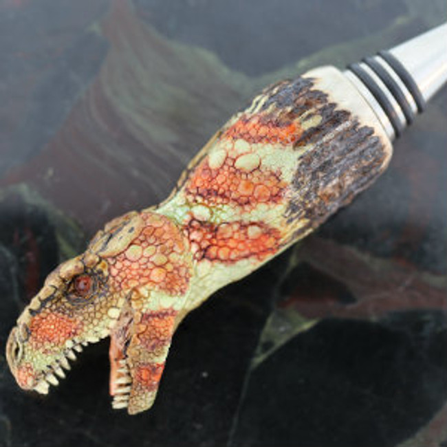 Bottle Stopper. Tyrannosaurus rex carved on India Sambar stag by Paul Grussenmeyer. Mozambique garnet eyes. Unscrews to allow use on other style stoppers, or as cane head. Stainless steel stopper. Left side.