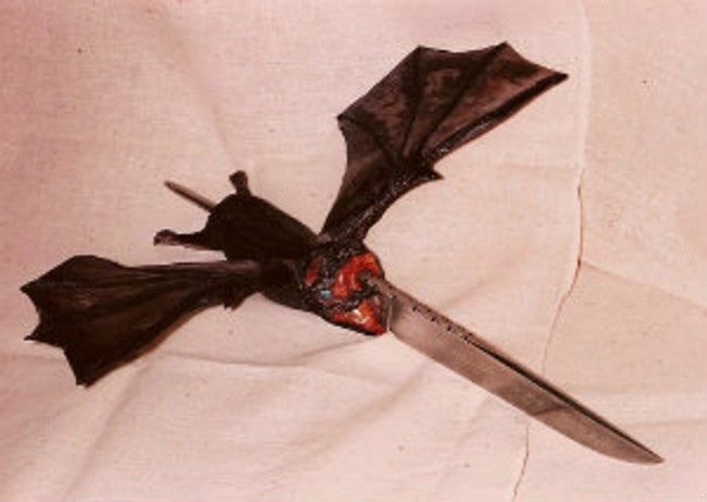 """Vampire Slayer"".  A full size vampie bat carved from American Moose antler stag mounted on a forged damascus blade knife by master carver Paul Grussenmeyer.  A nice display piece. Blade forged by J.D. Smith. Opal eyes, with painted pupils, ivory fangs, 8.5"" blade, 16"" overall, 13.75"" wingspan."