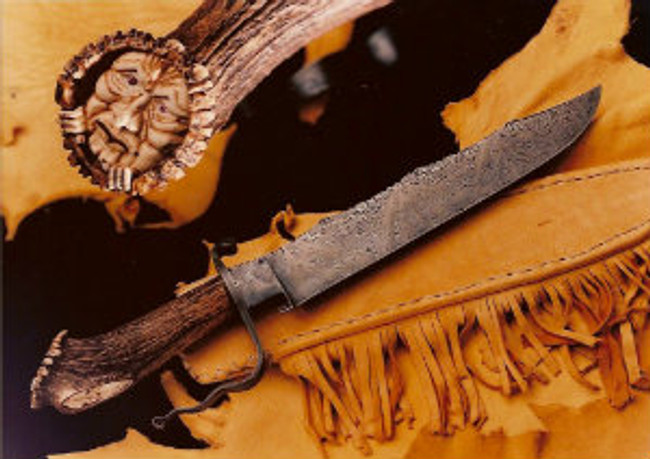 """Weeping Warlock"". Carving of a forest being on the India Sambar crown stag handle on a Daniel Winkler forged damascus knife. 11"" scalloped-back longknife blade wit full fileworked back, 17.5"" overall length, curled damascus guard, African pink tourmaline eyes, emerald in the naval, sheath and display stand."
