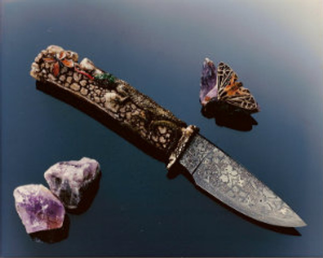"""Butterfly Hunter"". A fully carved India Sambar stag handle on a forged damascus knife by Master bladesmith, Hank Knickmeyer. This knife features a lizard crawling over rocks with its tongue extended in pusuit of a butterfly meal. Ruby eyes, 4.13"" mosaic (butterflies, flowers, spiderwebs, and HK's) damascus blade, twist pattern edge, carved cast bronze guard, 9.38"" overall length. With a nice display stand."
